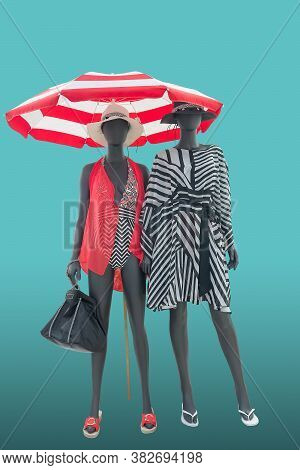 Two Full Length Female Mannequins Dressed In Fashion Beachwear, Isolated On Blue Background. No Bran