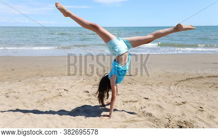 Girl Does Gymnastics On The Beach With A Pirouette And Legs In The Air