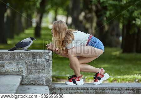 Young Woman Is Communicating With Tamed Crow In The Public Park. Blonde Caucasian Female In Her 20s