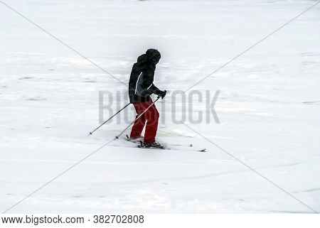 Active Man Ski Riding On Slope. Male Freeride Skier Moving On White Snow. Side View Of Male In Gray