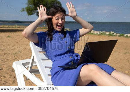 Girl Greeting During Videocall On Laptop Sitting In On The Beach. Freelancer And Blogger Participate