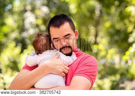 Father With Closed Eyes Tenderly Hugging Infant Daughter In Pink Jumpers Outdoors In Warm Sunny Or E