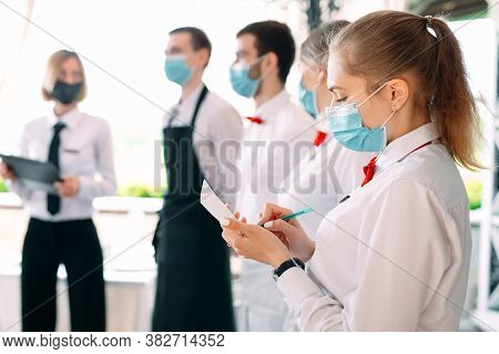 Employees Of A Restaurant Or Hotel In Protective Masks. End Of Quarantine. Restaurant Manager And Hi
