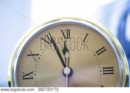 On A Clock With Roman Numerals From Five To Twelve. New Year New Day New Life Concept