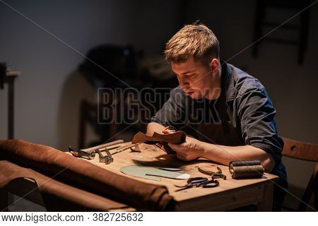 A Young Shoemaker In A Shoe Shop Makes Shoes From Leather With His Own Hands