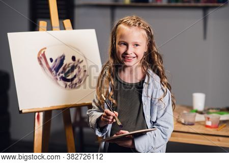 First Lesson In Art School, A Little Girl Learns To Draw And Makes Her First Oil Painting On Canvas