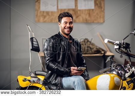 A Young Biker In A Leather Jacket In A Garage Smiles For A Photo And His Blog
