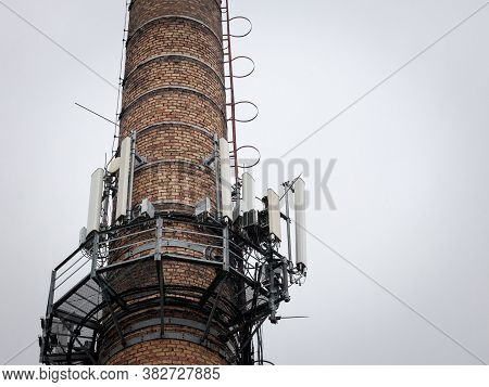 Mobile Phone Base Station, On An Old Industrial Brick Chimney Equiped With 3g, 4g And 5g Antenna, At