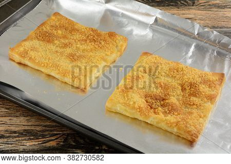 Baked Puff Pastry Sheets Sprinkled With Parmesan Cheese On Aluminum Foil On Baking Sheet