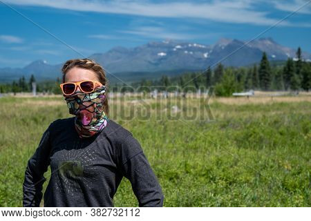 Cute, Wholesome Adult Woman With Braided Hear Poses In A Meadow In Polebridge Montana. Neck Gaiter (