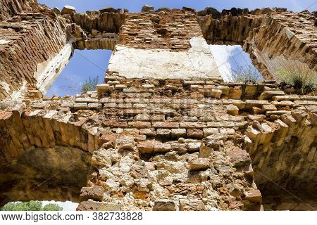 Empty Window Openings In An Abandoned Ruined Red Brick Building, The Ruins Of A Fortress In Europe