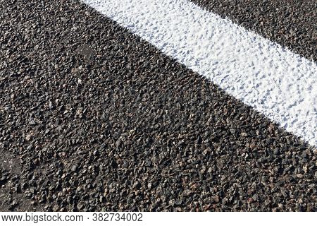 Close-up Of An Asphalt Road With White Road Markings Painted On It, A Road For Cars And Other Types