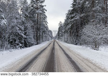 Narrow Paved Snow-covered Winter Road For Car Traffic, Overcast Sky On The Road, Snow On The Road Is