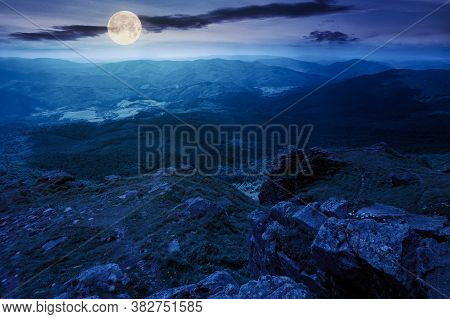 Rock On The Grassy Slope At Night. Summer Landscape In Mountains In Full Moon Light. Ridge In The Di