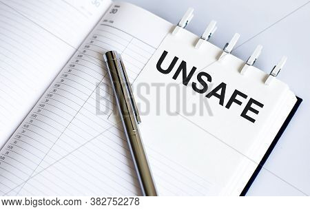 Unsafe On The Short Note Texture Background With Pen. Business Concept