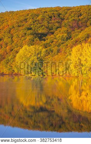 Mountain Lake Among The Forest. Trees In Colorful Foliage. Beautiful Landscape On A Sunny Autumn Mor