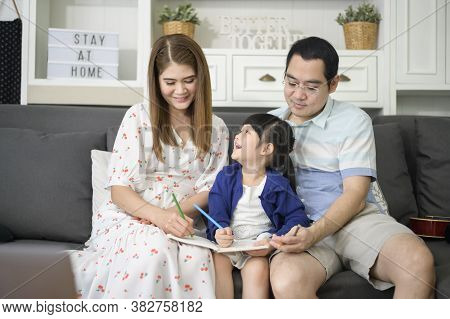 Happy Asian Parent Teaching Little Cute Daughter To Do Homework And Drawing Picture Together At Home