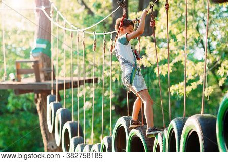 Rope Park. A Boy Passes An Obstacle On Tires In A Rope Park.