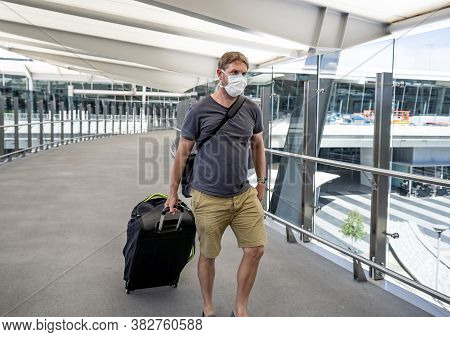Traveler With Protective Face Mask At Airport Terminal Worried Of Quarantine. Covid-19 And Travel