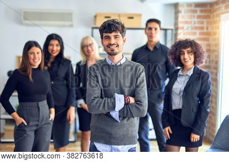 Group of business workers smiling happy and confident. Posing together with smile on face looking at the camera, young handsome man with crossed arms at the office