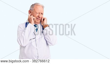 Senior handsome grey-haired man wearing doctor coat and stethoscope covering ears with fingers with annoyed expression for the noise of loud music. deaf concept.