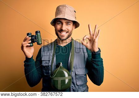 Young handsome tourist man with beard on vacation wearing explorer hat using binoculars doing ok sign with fingers, excellent symbol