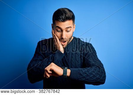 Young handsome man wearing casual sweater standing over isolated blue background Looking at the watch time worried, afraid of getting late