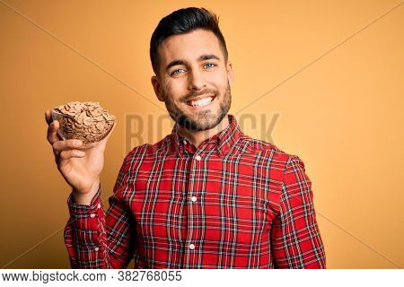 Young handsome man eating classic wholemeal cereals over yellow background with a happy face standing and smiling with a confident smile showing teeth