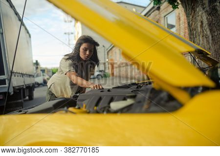 Young Woman Stands Near Yellow Car With Opened Bonnet And Repairs It Against Background Of Building.