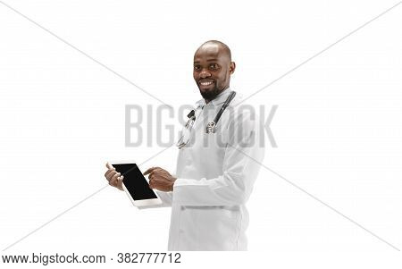 Pointing On Screen. African-american Doctor Isolated On White Background, Professional Occupation. D