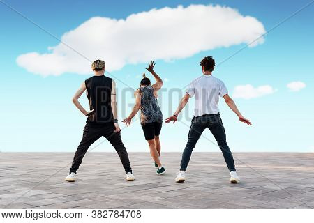 Three Unrecognizable Young Men Dancing Sport Dances, Hip-hop Or Break-dance Outdoors. Teenage Lifest