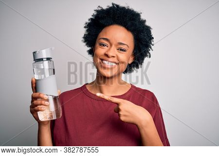 Young African American afro woman with curly hair drinking bottle of water for refreshment very happy pointing with hand and finger