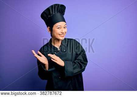 Young beautiful chinese chef woman wearing cooker uniform and hat over purple background clapping and applauding happy and joyful, smiling proud hands together