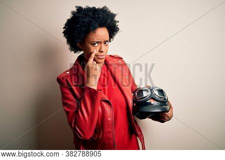 Young African American afro motorcyclist woman with curly hair holding motorcycle helmet Pointing to the eye watching you gesture, suspicious expression