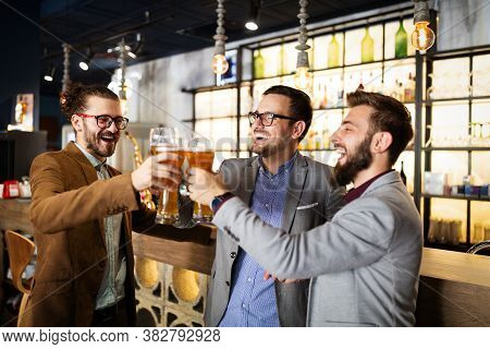 Leisure, Friendship Pub Concept. Happy Male Friends Drinking Beer And Clinking Glasses At Bar Or Pub