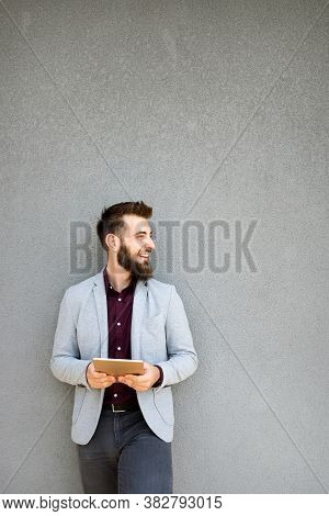 Happy Young Business Male Executive Using Digital Tablet Against Gray Background