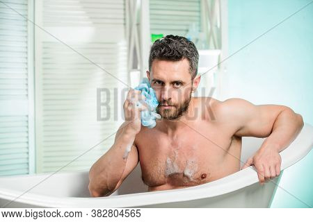 Hygiene And Health. Guy In Bathroom With Toiletries Man Wash Muscular Body With Foam Sponge. Persona