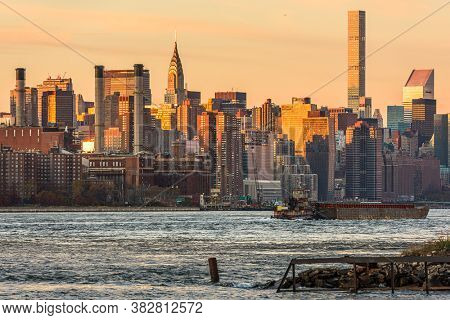 New York, New York, USA midtown Manhattan cityscape from across the East River at dusk.