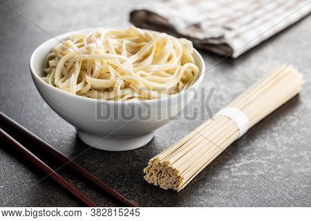 Cooked udon noodles. Traditional Japanese noodles in bowl on black table.