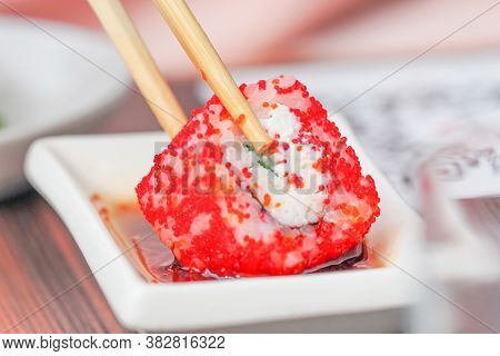 Chopsticks Taking Portion Of Sushi Roll. Sushi Maki Roll With Chopsticks And Soy Sauce, Close-up