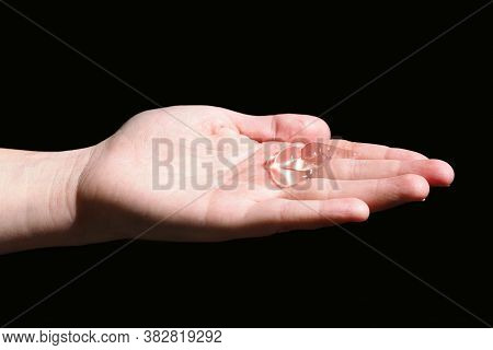 Disinfection Gel On The Palm. Hand Isolated On Black Background. Disinfecting Hands. Taking Disinfec