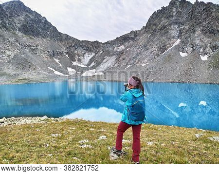 Young Active Woman With Photographic Camera Taking Photo At Blue Water Background. Imeretinsky Lake