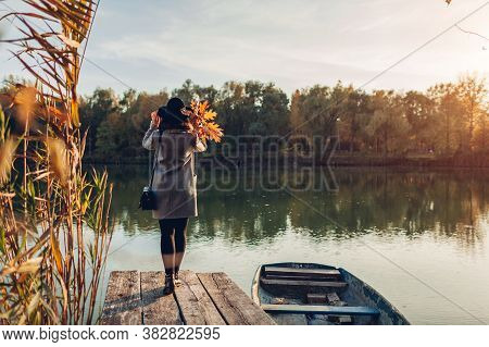 Woman Walking On Lake Pier By Boat Admiring Autumn Landscape Holding Leaves. Fall Season Activities