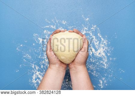 Leavened Raw Dough Held In Hand Over A Blue Table. Flat Lay With Woman Holding Bread Dough. Hand-kne