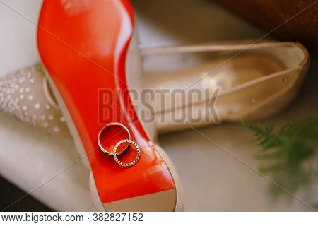 Close-up Of Wedding Gold Rings On Red Soles Of Ballet Flats For The Bride On A Blurred Background.