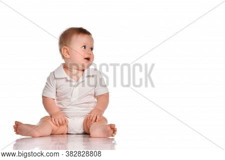 Curious And Inquisitive Toddler Boy Dressed In A White Bodysuit Sits Barefoot, Looking At The Free S