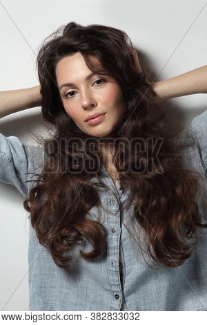 Young beautiful woman with long curly hair and natural makeup