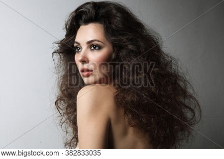 Young beautiful woman with long curly hair and smoky eye makeup