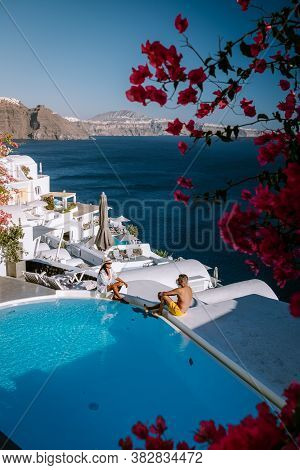 Santorini Greece, Young Couple On Luxury Vacation At The Island Of Santorini Watching Sunrise By The