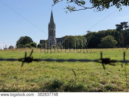 Church Steeple Against Blue Sky In Distance Over Grassy Field In Foreground And Closeup Of Barbed Wi